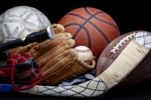 Close up shot of old soccer ball, basketball, baseball, football, bat, hockey stick, baseball glove and cleats